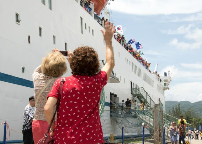 Jamaica: Montego Bay, Jamaica :: Attendees of OM Ships Presidential Briefing wave to crewmembers with flags before walking up the conference gangway. More Info