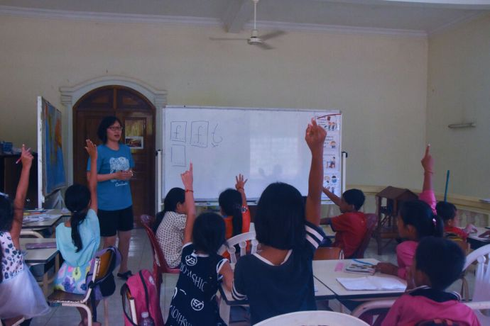 Cambodia: Students eagerly volunteer to practice writing letters on the white board in a free English class that MTI Cambodia offers to children from low-income homes. More Info