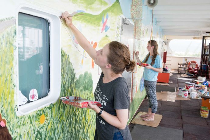 Jamaica: Montego Bay, Jamaica :: Renske Cloosterman (left) and Anna Bolte (both Netherlands) paint a mural on the Fun Deck for school-aged children who live on Logos Hope. More Info