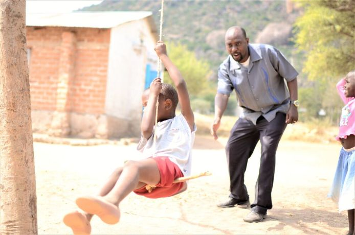 Tanzania: Pastor Jacob Makorere pushes a child from his church on a swing. More Info
