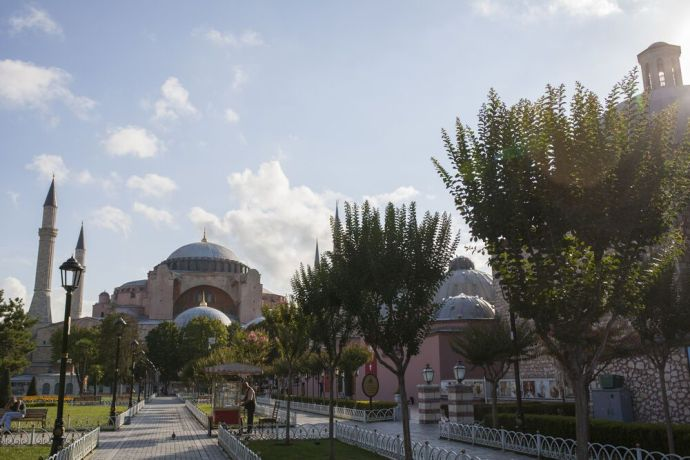 Turkey: The famous Byzantine basilica turned mosque turned museum, the Hagia Sophia sits in the heart of Istanbul. In the morning hours a man prepares his cart to sell warm simit, a bread covered in sesame seeds. More Info