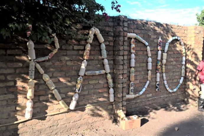 Malawi: The wall outside the Radio Lilanguka studio features a sign made out of bottles More Info