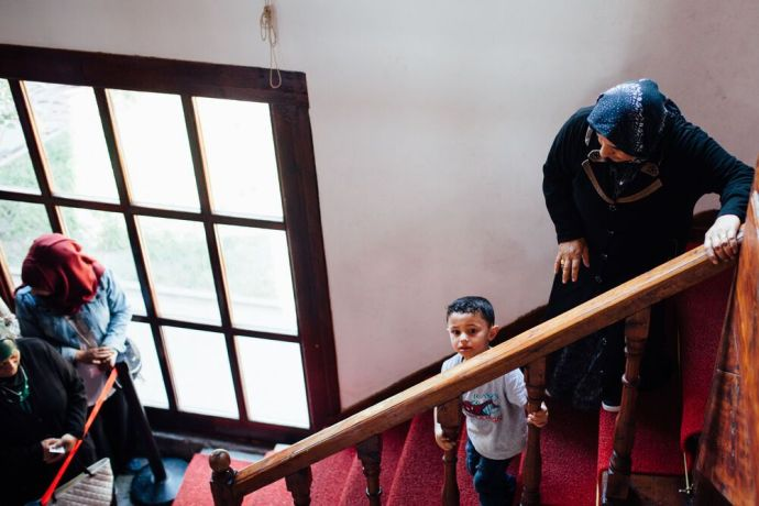 Turkey: A woman and young boy make their way down the steep stairs at a refugee centre in Turkey. More Info