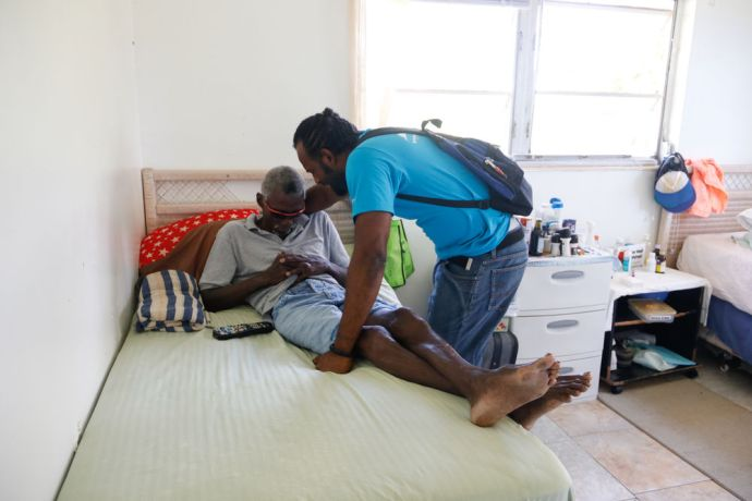 Bahamas: Freeport, The Bahamas :: Freddy Bijoux (Seychelles) prays for a man at a home for elderly people. More Info