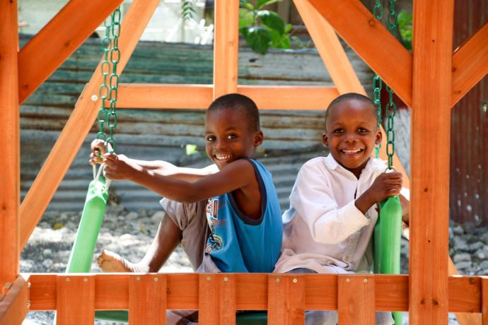 Haiti: Port-au-Prince, Haiti :: Children play on a swing after crewmembers build a playground for their school. More Info