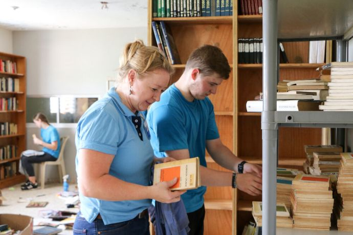 Dominican Republic: Santo Domingo, Dominican Republic :: Theresa Kempfer (Germany) and Philip Harper (UK) arrange books on shelves while cleaning a communitys library. More Info