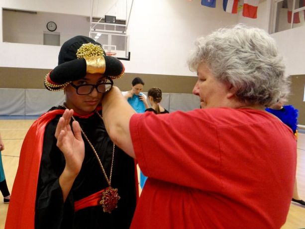 Hungary: OMer Rebecca Lingenhoel helps a Hungarian student adjust his costume during a drama camp outreach. More Info