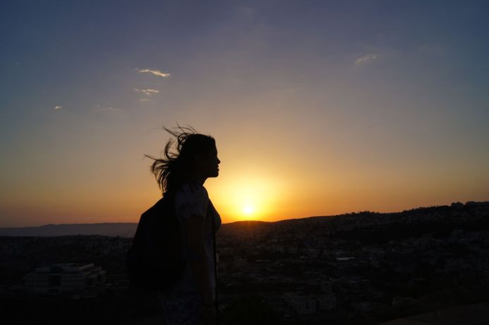 Israel: A woman stands in silhouette at sunset. More Info