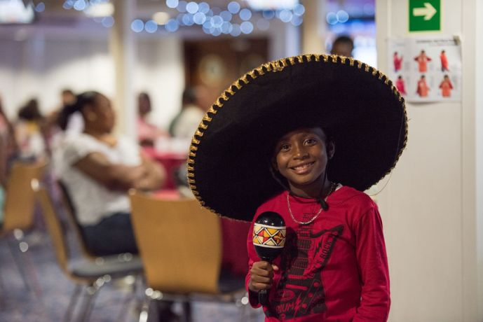 Antigua & Barbuda: St. Johns, Antigua and Barbuda :: A local child tries on a Mexican costume during a cultural event on board. More Info