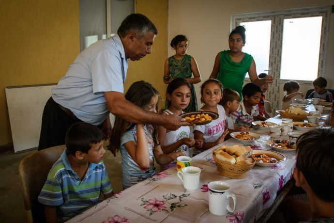 Romania: Pastor Marian serving children of his community in Romania with possibly their only hot meal of the day.  Photo by Garrett N More Info