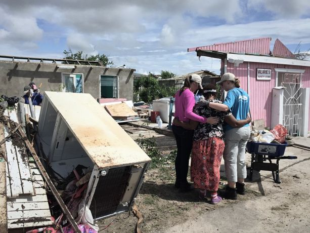 Antigua & Barbuda: St Johns, Antigua and Barbuda :: Logos Hope's crewmembers pray for Valarie, a Barbudan shop owner, at her business which was ruined by Hurricane Irma. More Info