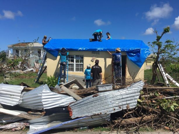 Antigua & Barbuda: St Johns, Antigua and Barbuda :: Logos Hope crewmembers help cover a roof with tarpaulin alongside relief workers from Samaritans Purse. More Info