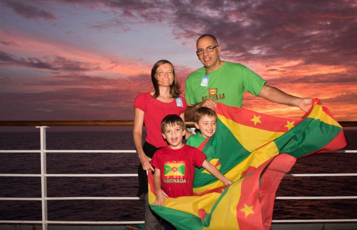 Saint Lucia: Castries, St. Lucia :: Adi (Grenada), Catherine (New Zealand), Noah (UK) and Asher de Freitas (UK) with Grenada flags on the outer deck at sea. More Info