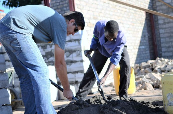 Malawi: Two men mix cement to make into bricks in Malawi. More Info