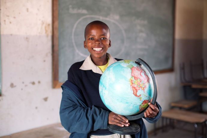 Lesotho: Boy holds globe in a school in Lesotho. More Info