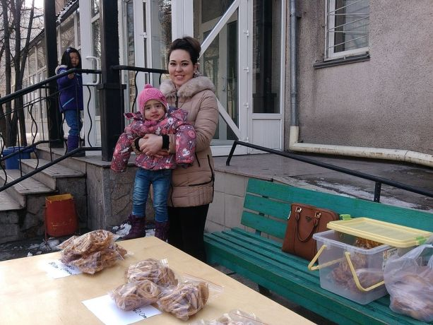 Central Asia: A mother and her young daughter sell baked goods in front of a shop More Info