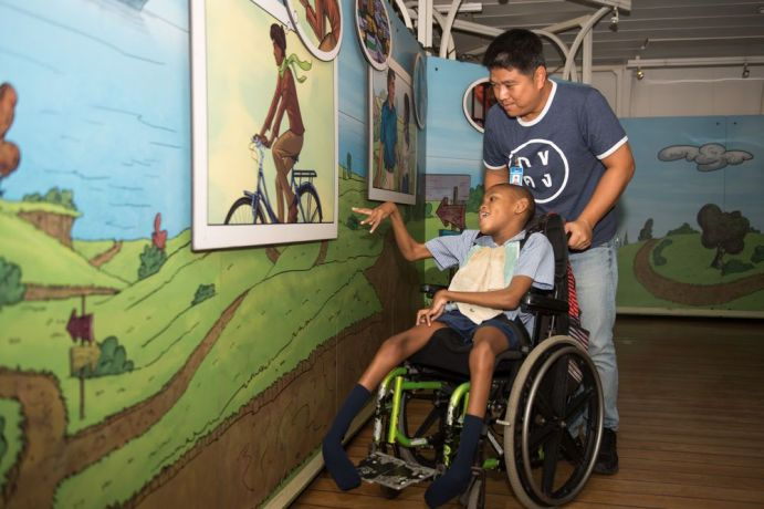 Barbados: Bridgetown, Barbados :: Boaz Pathsuthichote (Thailand) explains the Journey of Life display to a disabled student. More Info