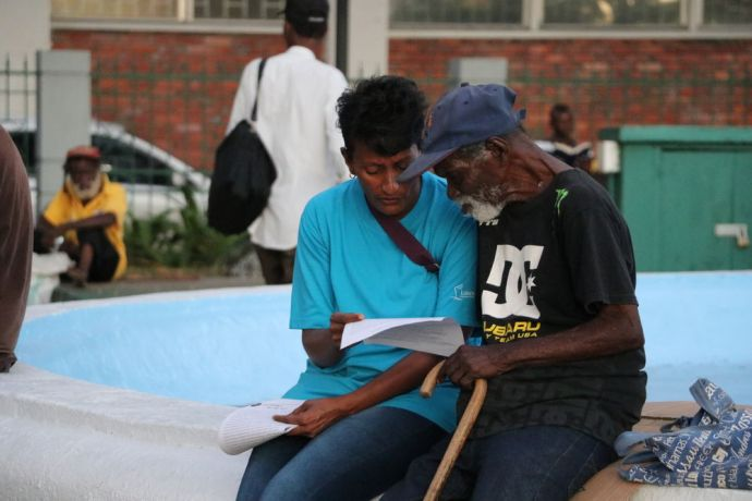 Barbados: Bridgetown, Barbados :: Sarah Chetty (South Africa) reads to a homeless man. More Info