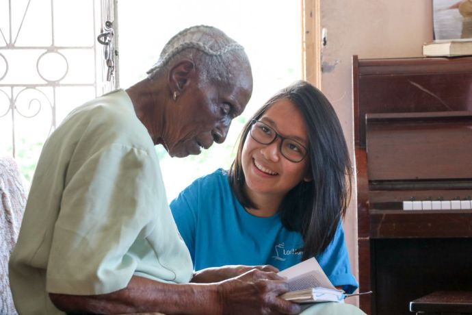 Saint Vincent & the Grenadines: Kingstown, St. Vincent and Grenadines :: Jade Wong (East Asia Pacific) helps a woman to choose a song. More Info