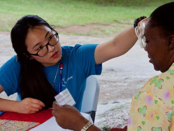 Grenada: Saint Georges, Grenada :: YeaSel Jo (South Korea) tests the eyes of a staff member at an elderly care home. More Info