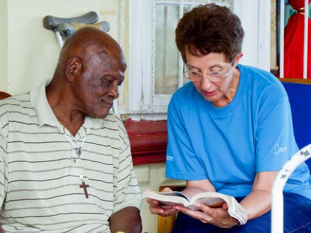 Grenada: Saint George, Grenada :: Sue de Villiers (South Africa) reads the Bible for an elderly man. More Info