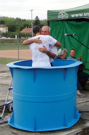Hungary: OM sports ministry leader Terry Lingenhoel (USA) hugs player Krisztián Tóth after baptising him at the baseball field. More Info