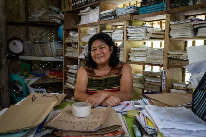 Philippines: A woman poses in a village tutoring book storeroom of OMs Alternative Learning School. More Info
