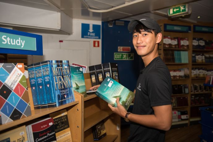 Grenada: Saint Georges, Grenada :: Abram Gim (South Korea) puts Spanish books on shelves in preparation for the Latin America visit. More Info