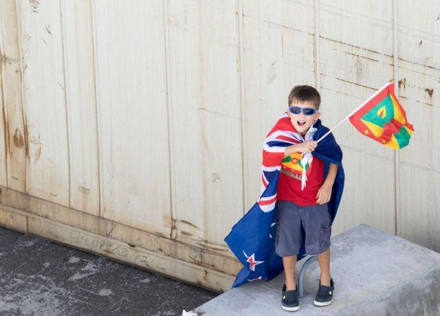 Grenada: Saint Georges, Grenada :: Noah De Freitas (UK) waves a Grenada flag as the ship leaves port. More Info