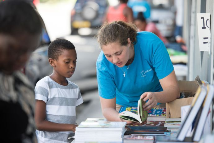Grenada: Saint Georges, Grenada :: Ly-Mari Marais (South Africa) helps a boy to select books. More Info