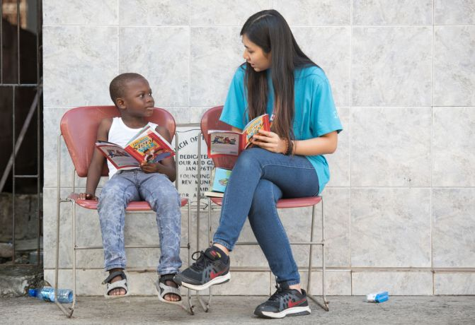 Grenada: Saint Georges, Grenada :: Tanya Ying (Thailand) reads a book with a boy. More Info