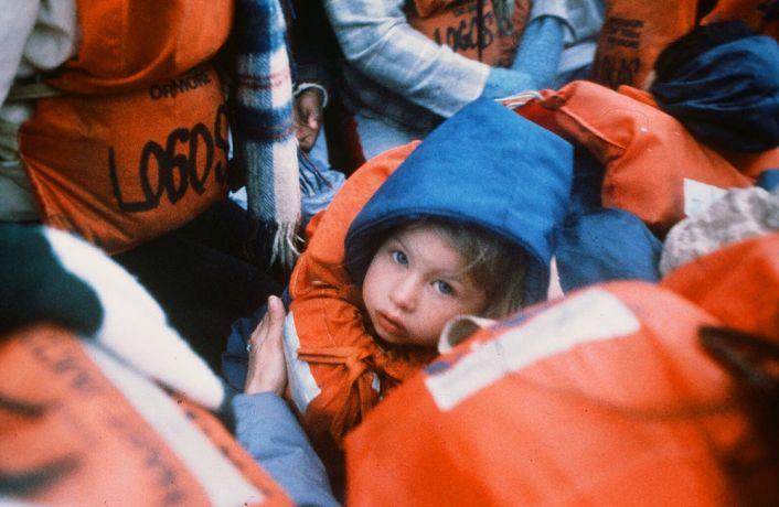 Ships: A child sits among Logos crewmembers abandoning ship. More Info
