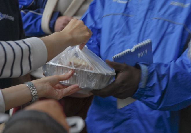 Greece: An OMer giving food to a homeless person during a weekly food distribution at a church in Athens, Greece. More Info