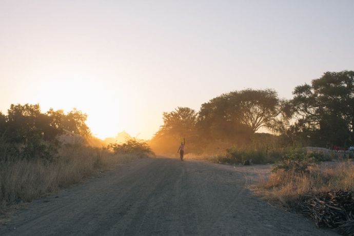 Namibia: A woman walks down a road in Namibia at sunset. More Info