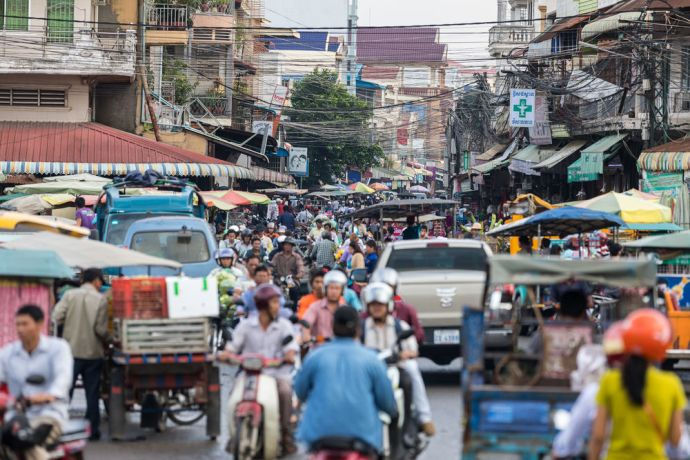Cambodia: People, tuk-tuks, mopeds and vehicles crowd the streets of Cambodia. Photo by Adrian Green More Info
