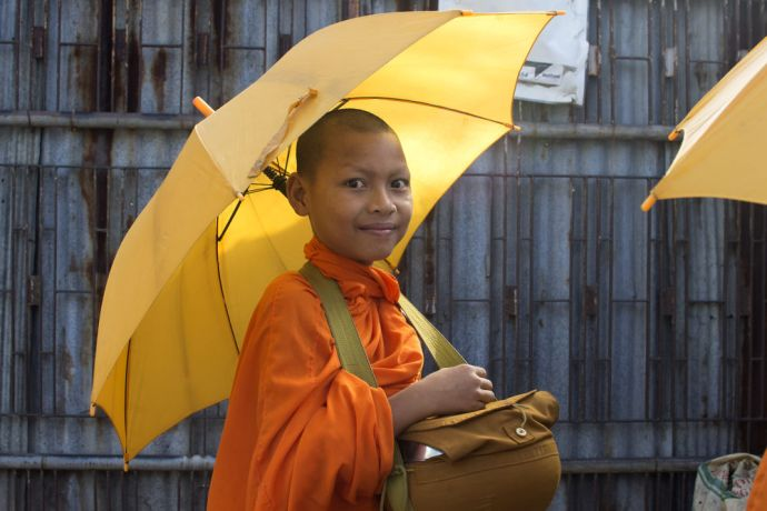 South East Asia: A young novice monk makes his morning rounds to collect alms - offering prayers in exchange for money and food gifts. More Info