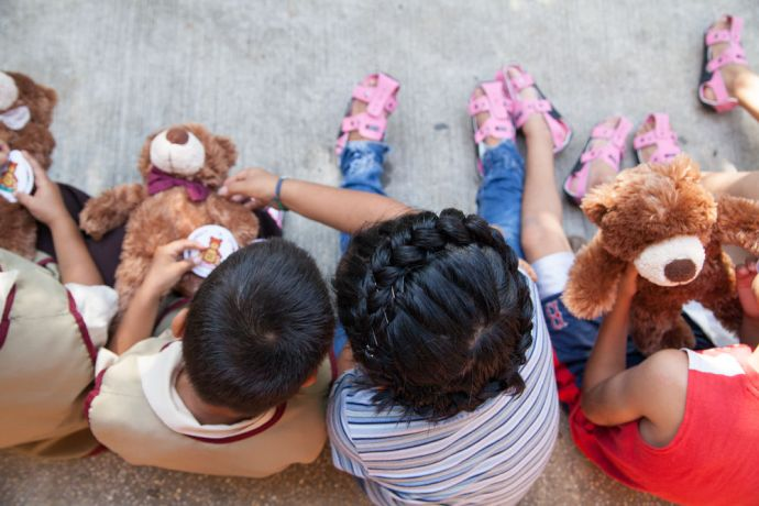 Guatemala: Puerto Barrios, Guatemala :: Children with new bears and pairs of The Shoe That Grows given to them by the Logos Hope team. More Info