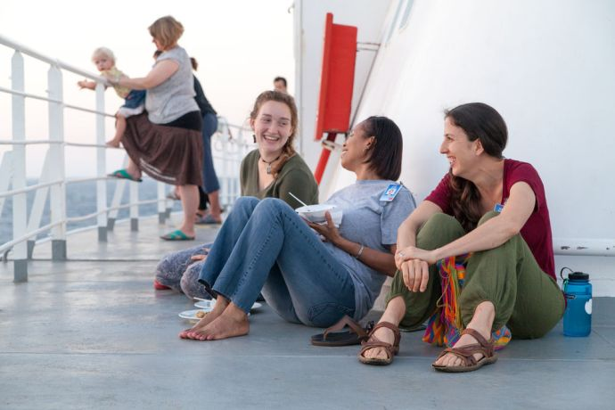 Ships: At Sea :: Nadine Betz (Germany), Susan Isidore (Trinidad and Tobago) and Melissa Martinez (Mexico) enjoy dinner outside on deck. More Info