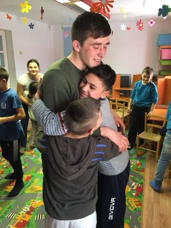 Romania: Petru (MD) loving the kids in Babadag, Romania, during his MDT-e3 outreach experience. More Info