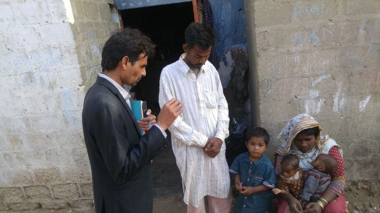 Pakistan: A team member prays for a local family. More Info