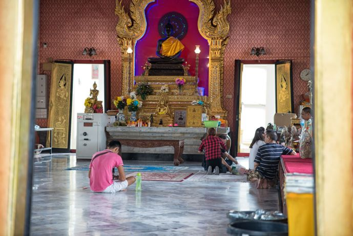 Malaysia: Several people talking to a monk in a Buddhist temple. More Info