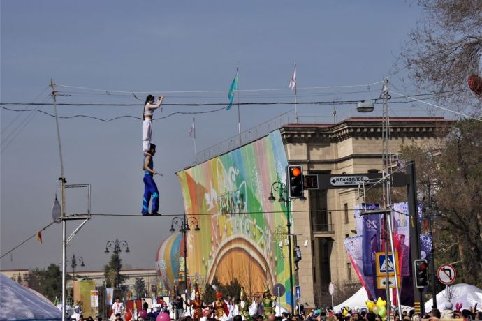 Central Asia: A pair of tightrope walkers balance above a crowd. More Info
