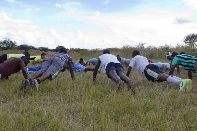 Zambia: A group of young men do planks together. More Info