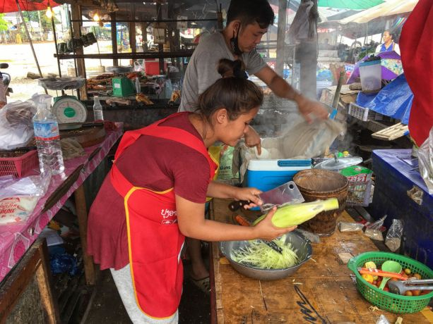 South East Asia: People working at their food stall in Laos. More Info