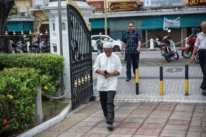 Malaysia: A man wearing traditional clothing as he heads to the mosque to answer the call to prayer during Ramadhan. More Info