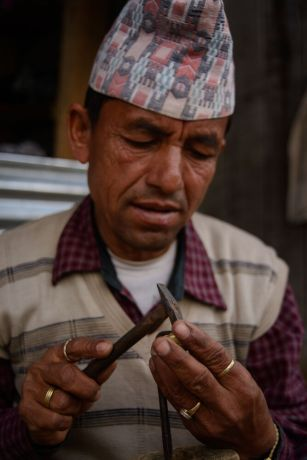 Nepal: A Nepali jeweler makes pieces of jewelry while sitting on the sidewalk in a remote village in Nepal. More Info