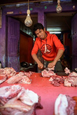Nepal: A young man smiles posing for his picture to be taken while cutting meat at a local butcher shop in Nepal. More Info