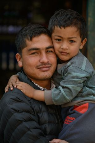 Nepal: A father tenderly holds his son in a remote village in Nepal.  Photo by Garrett N More Info