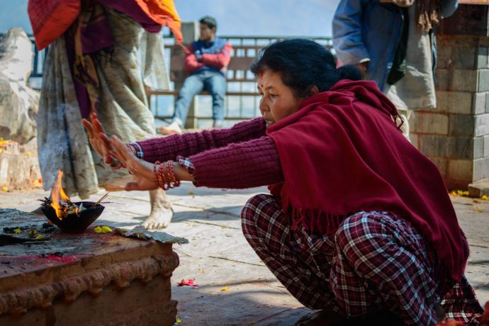 Nepal: A woman sits in front of an offering given at a Hindu temple in Kathmandu, Nepal. More Info