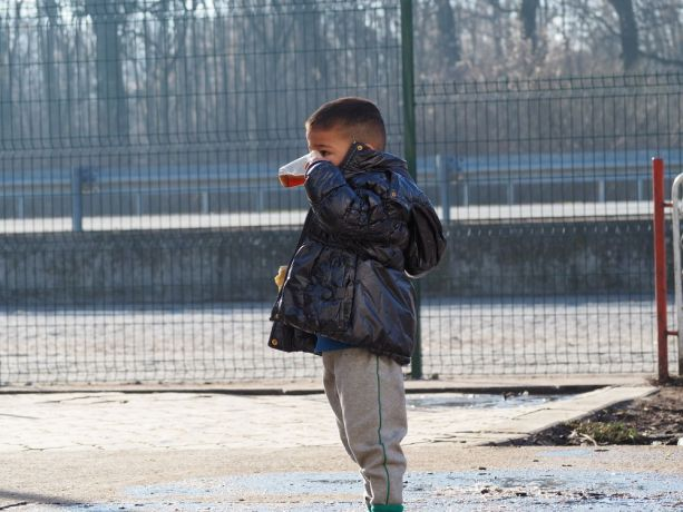 Serbia: A young boy enjoys a drink of tea at the refugee camp on the Serbian border More Info